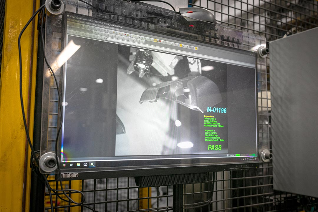 Automated vision system integrated to robot and press, detecting short shots.